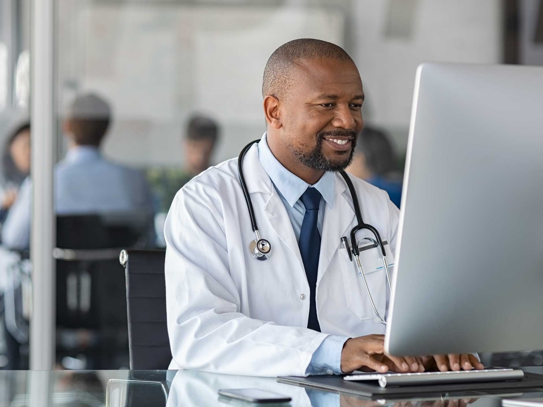 A doctor sitting at a desk, using a computer