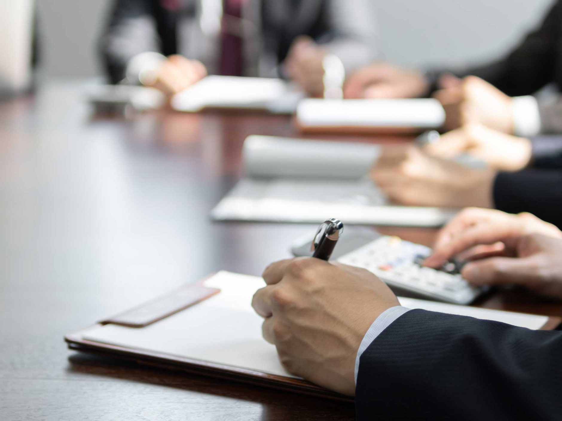 Someone writing on a clipboard, during a meeting